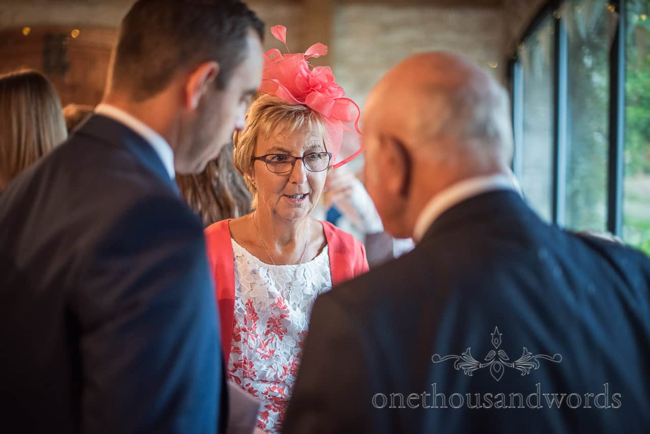 Wedding guest in pink fascinator and matching top enjoys talking to other guests at indoor drinks reception