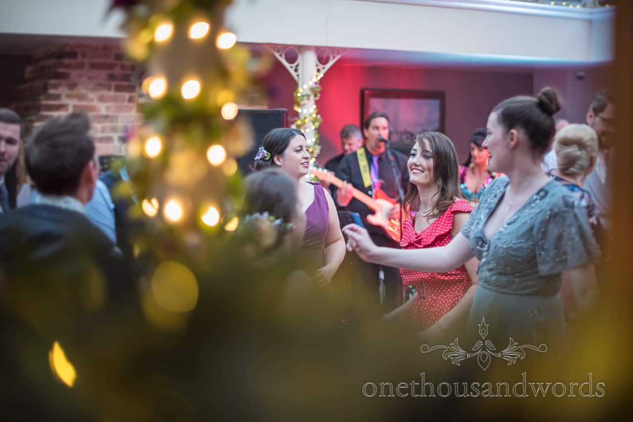Wedding guests dancing to band on wedding evening in venue with fairy lights and green foliage pole decoration photograph