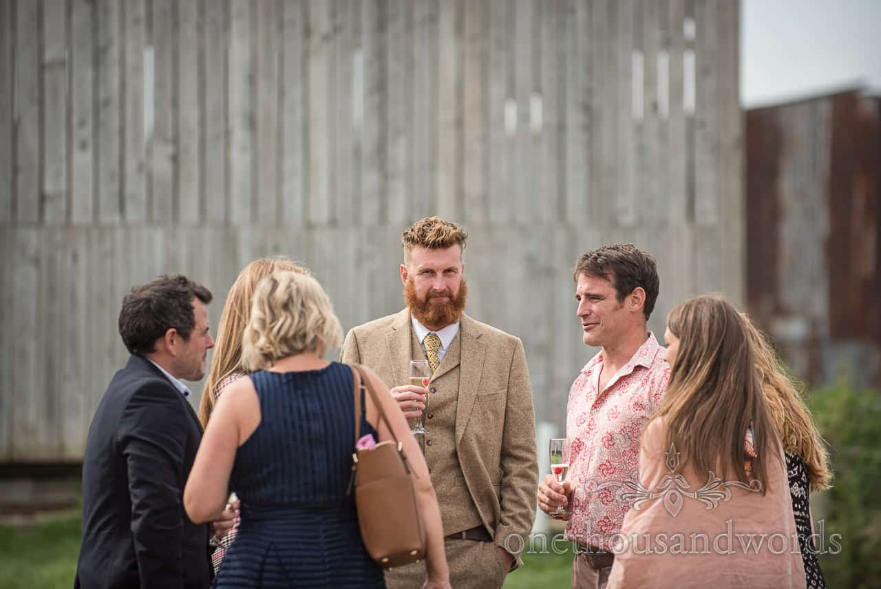 Dapper country gent wedding guest with beard wears brown tweed three piece suit at wedding drinks reception