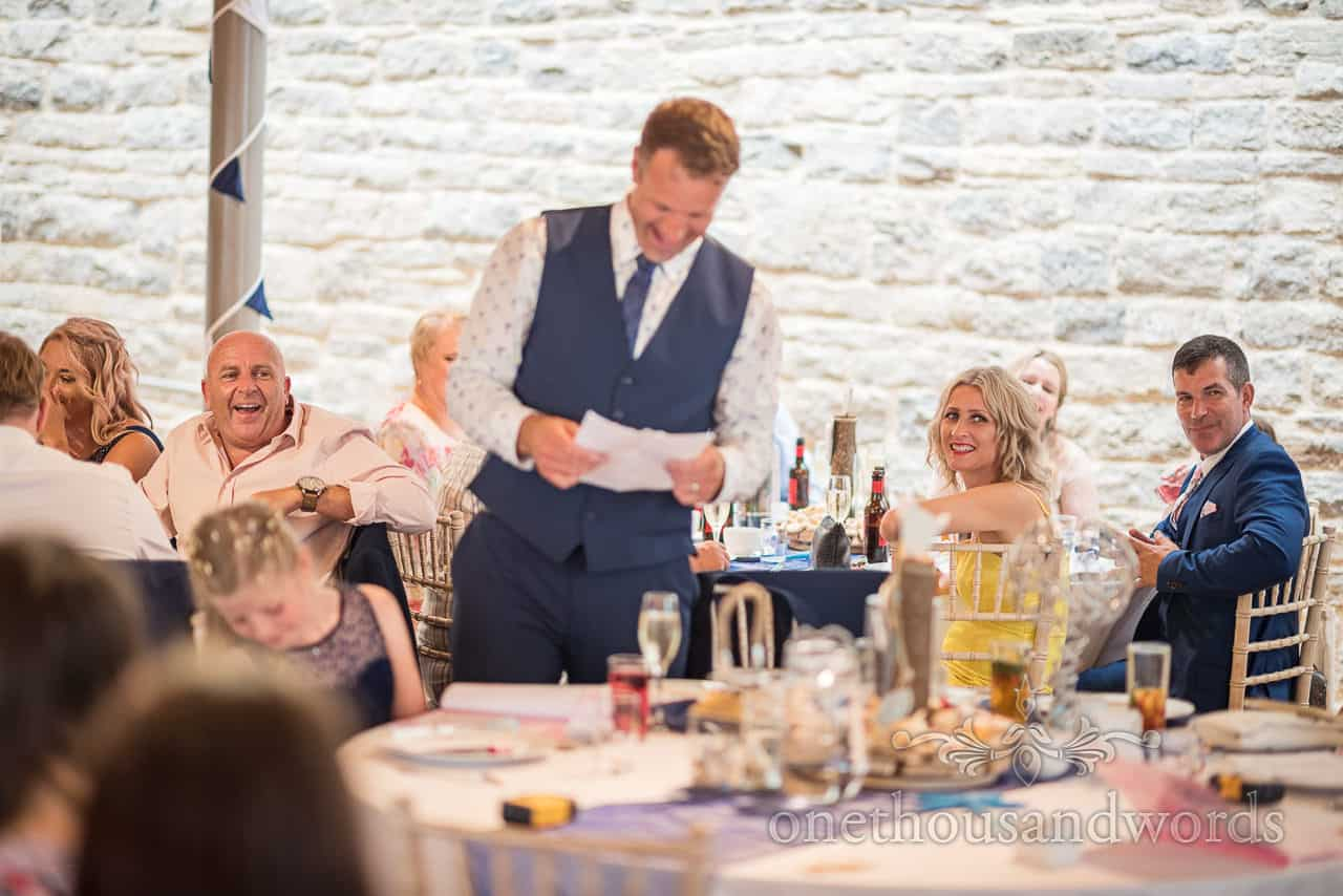 Wedding guests laugh at grooms speech in Durlston Castle gallery venue by one thousand words documentary wedding photography