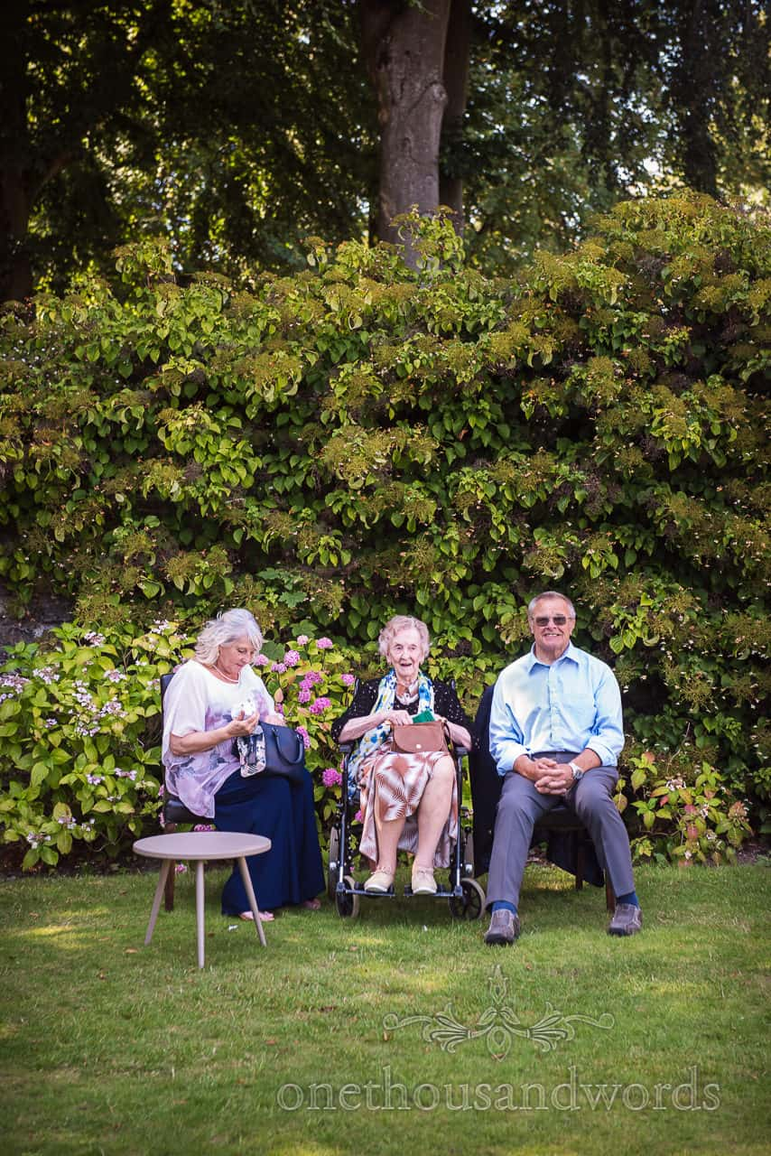 Wedding guests shelter from the summer sun in the shade of the gardens plants documentary wedding photograph by one thousand words