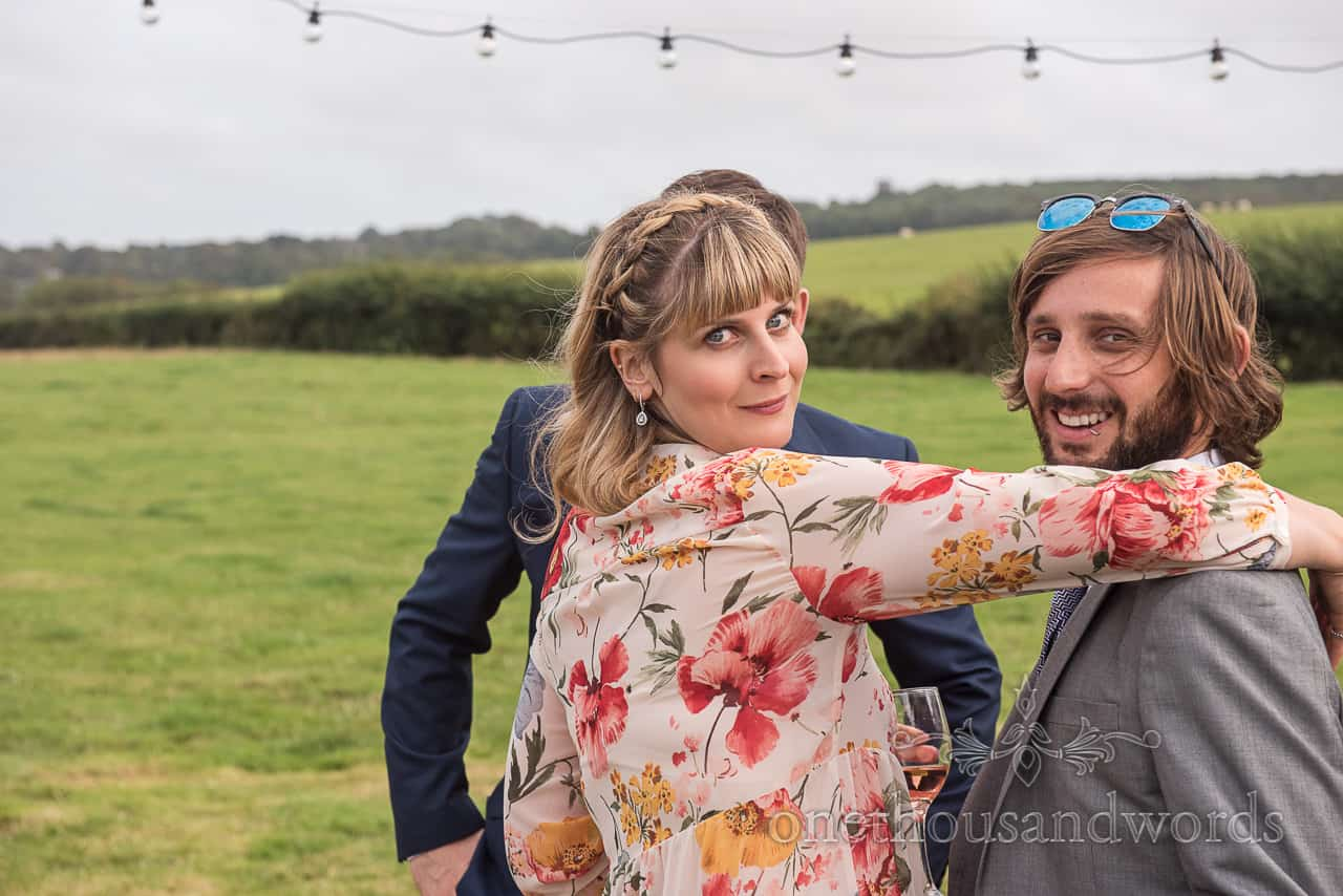 Wedding guest in floral dress strikes a pose during drinks reception in Dorset countryside field