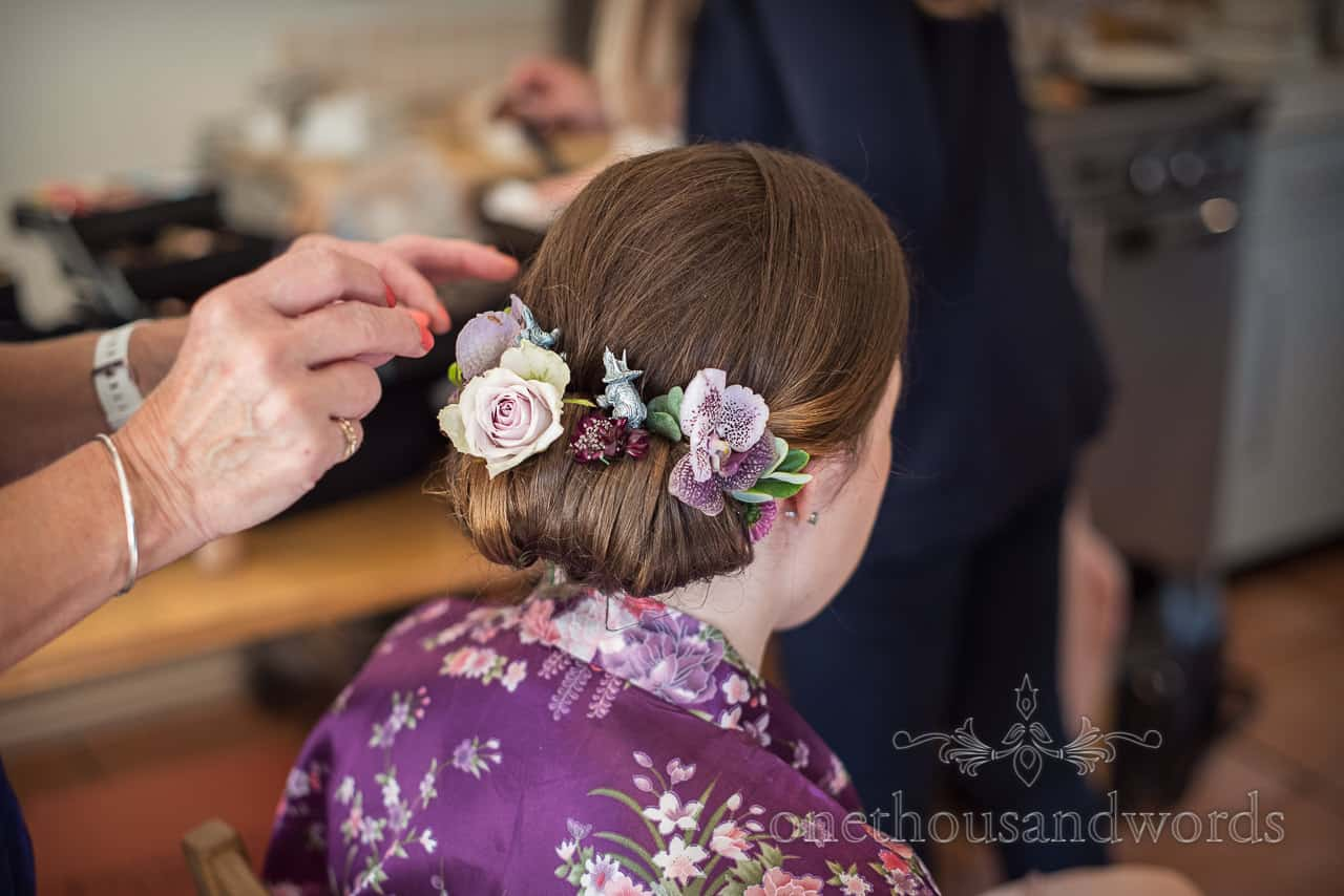 Bridesmaid in purple silk dressing gown wedding morning hair styling with dinosaur and flower additions photograph