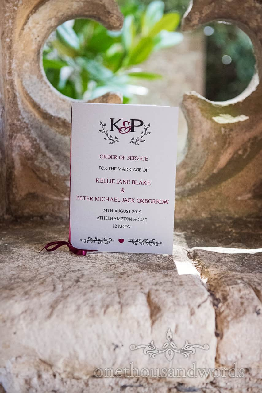White and purple berry coloured ribbon bound wedding order of service photograph by one thousand words wedding photography