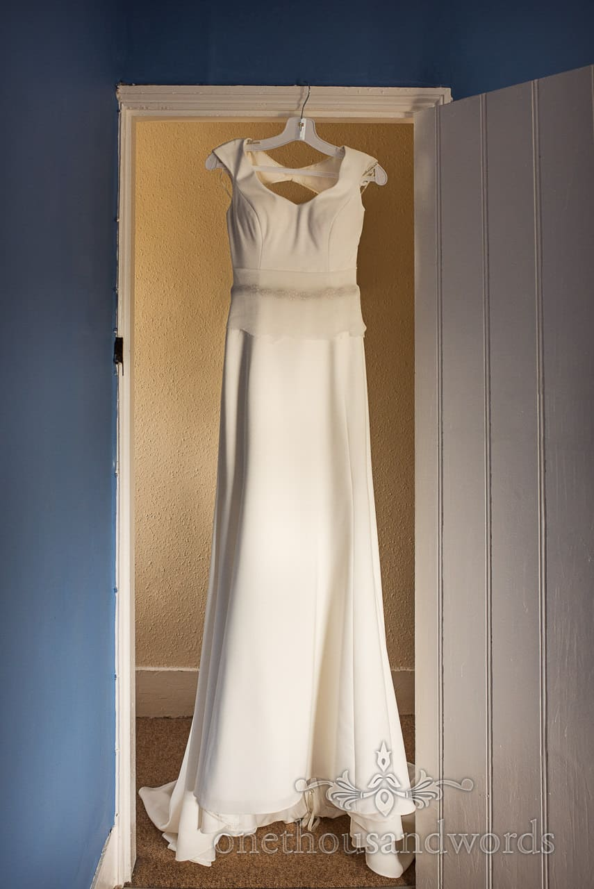 Simple and elegant white wedding dress hanging in doorway of blue room on wedding morning