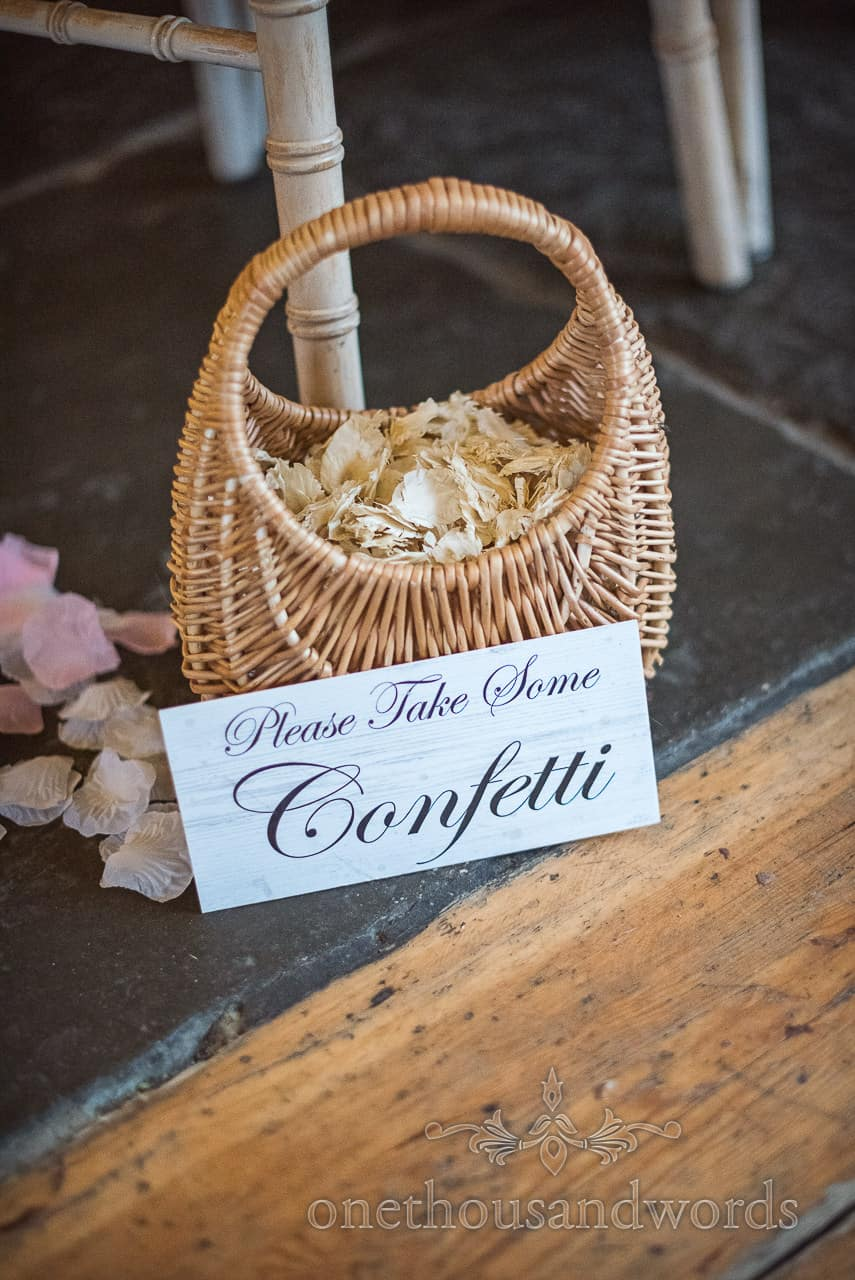 Wedding detail photograph of wicker basket of confetti with Please Take Some Confetti sign at barn wedding