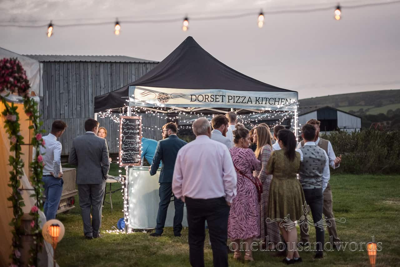 Wedding guests queue outside Dorset Pizza Kitchen at Purbeck farm marquee wedding evening reception