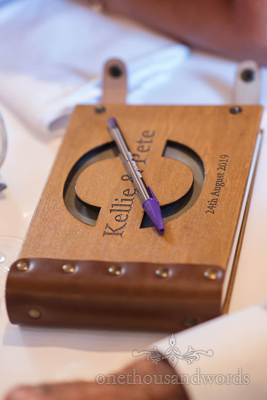 Wooden leather bound engraved wedding guest signing book with pen detail photograph by one thousand words wedding photographers