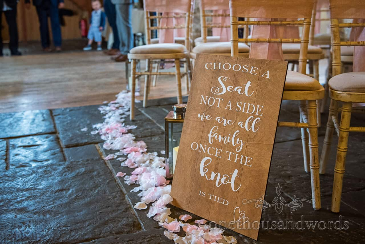 Choose A Seat Not A Side wooden signage in aisle at Kingston barn wedding detail photograph by one thousand words