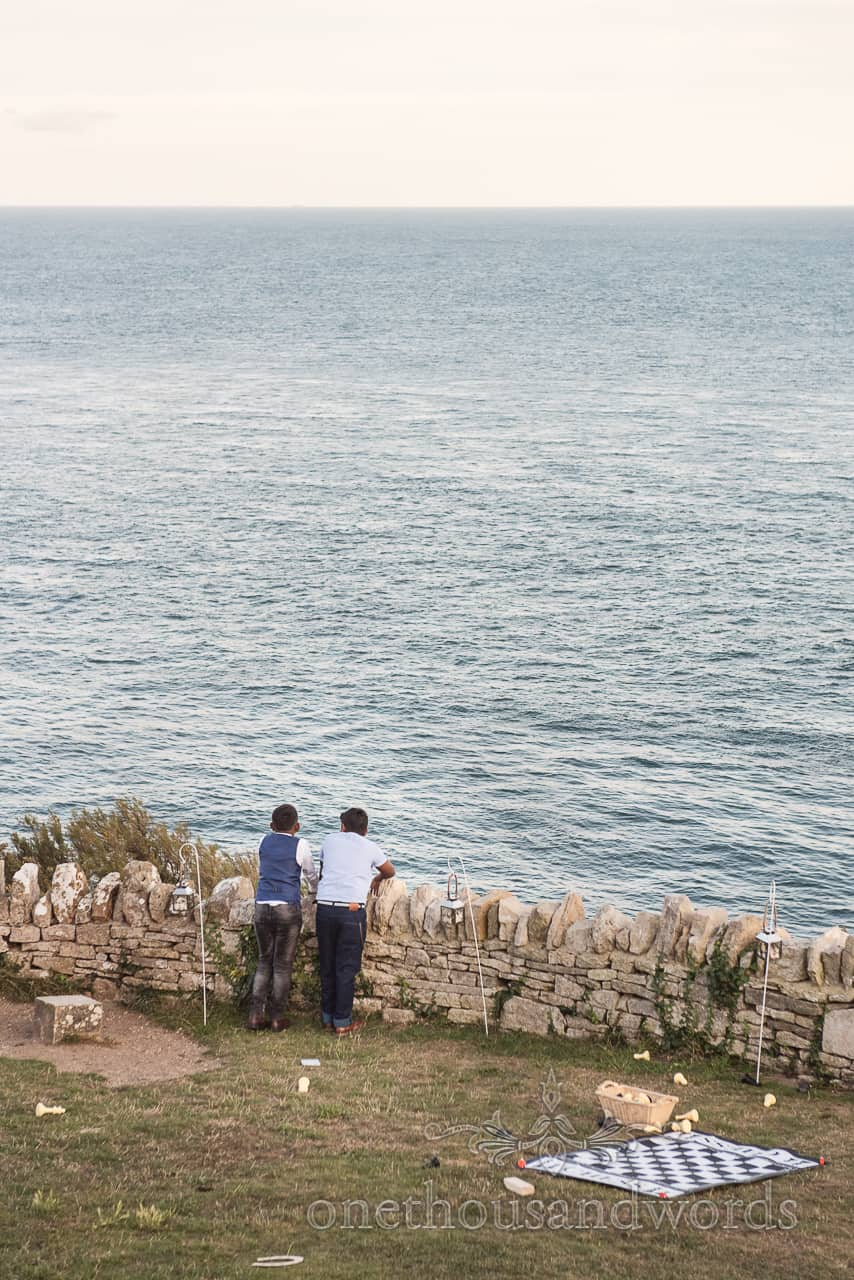 Young wedding guests ignore lawn games and look at the sea over a dry stone wall from clifftop garden at Purbeck castle wedding
