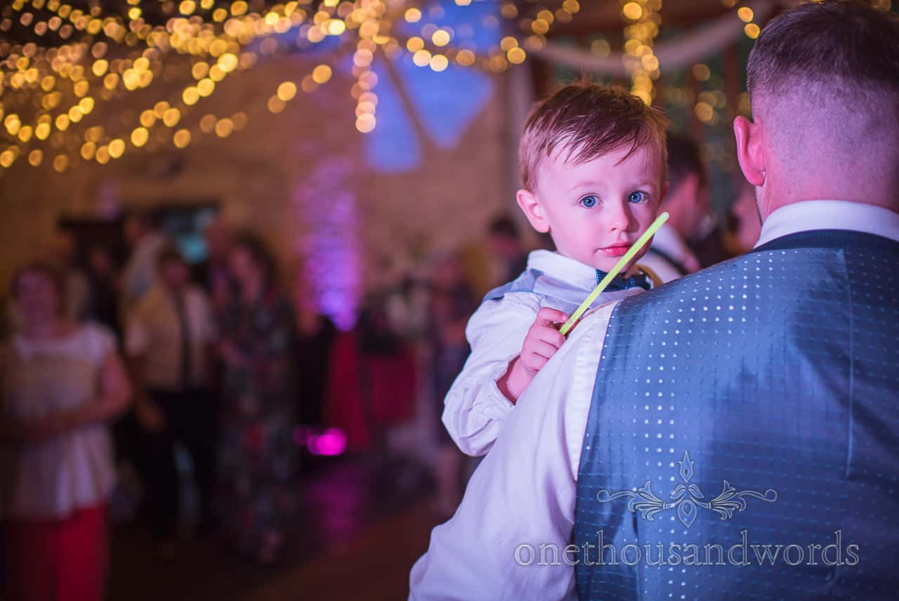 Young boy wedding guest is carried under disco lights and fairy lights at wedding barn evening reception photo by one thousand words