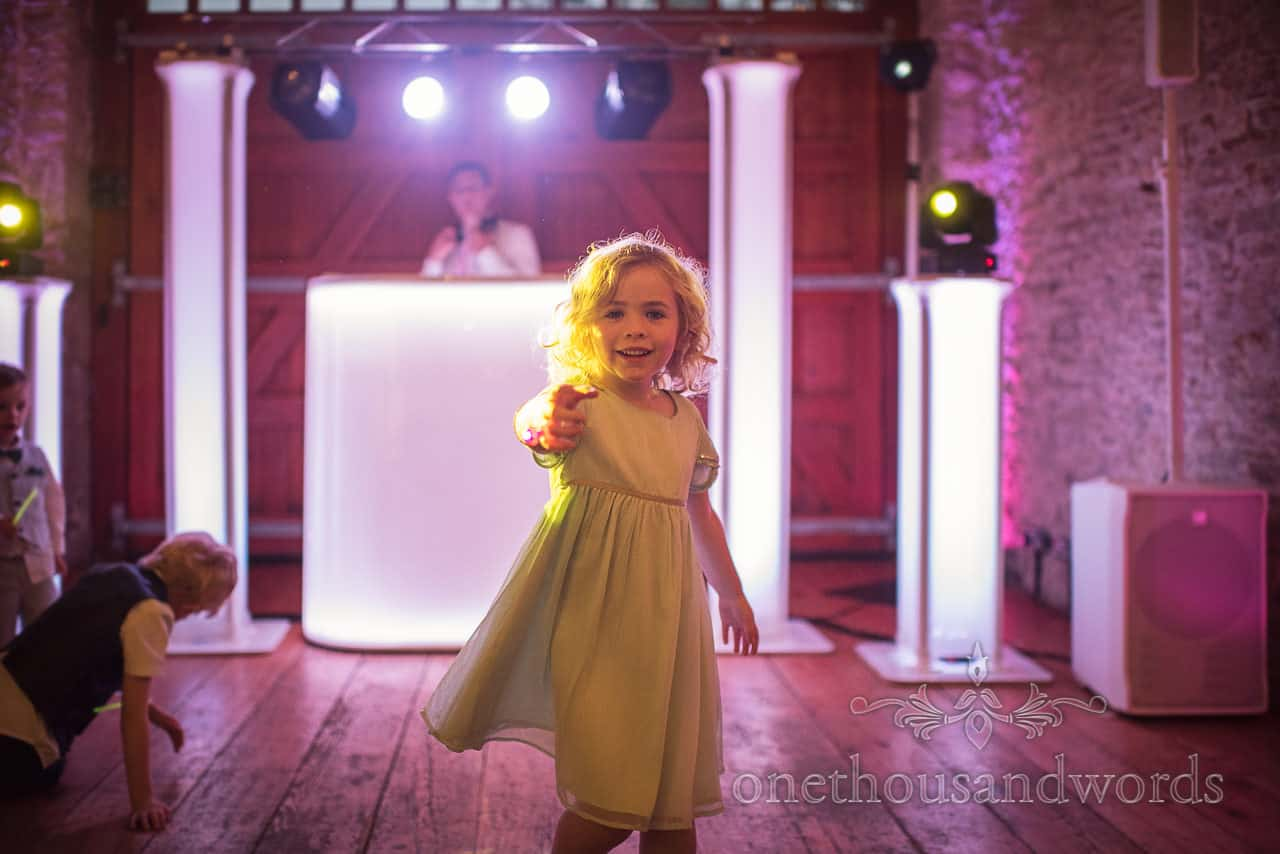 Young wedding guest dances on the dance floor with DJ at Kingston Country Courtyard wedding photo by one thousand words