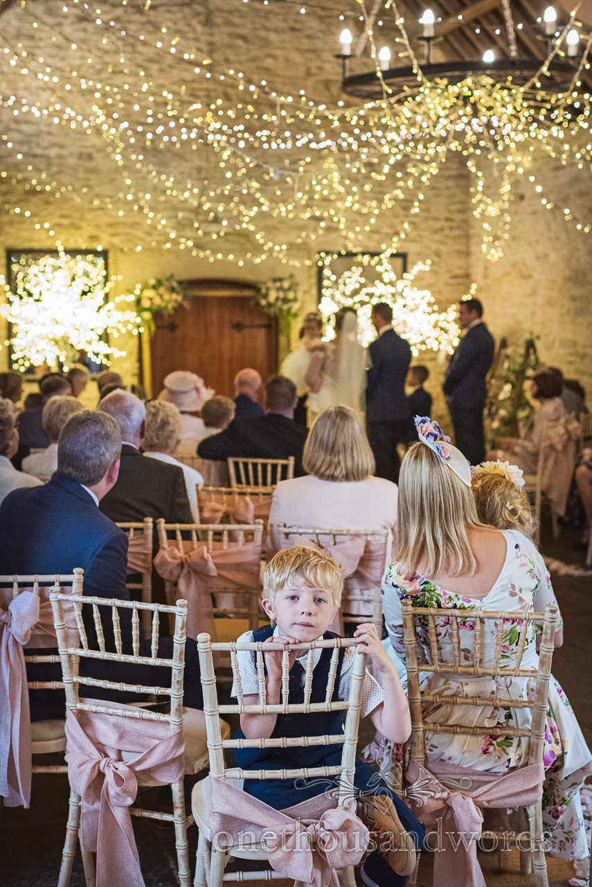 Young wedding guest photographed during Kingston barn wedding ceremony by one thousand words wedding photographers in Dorset