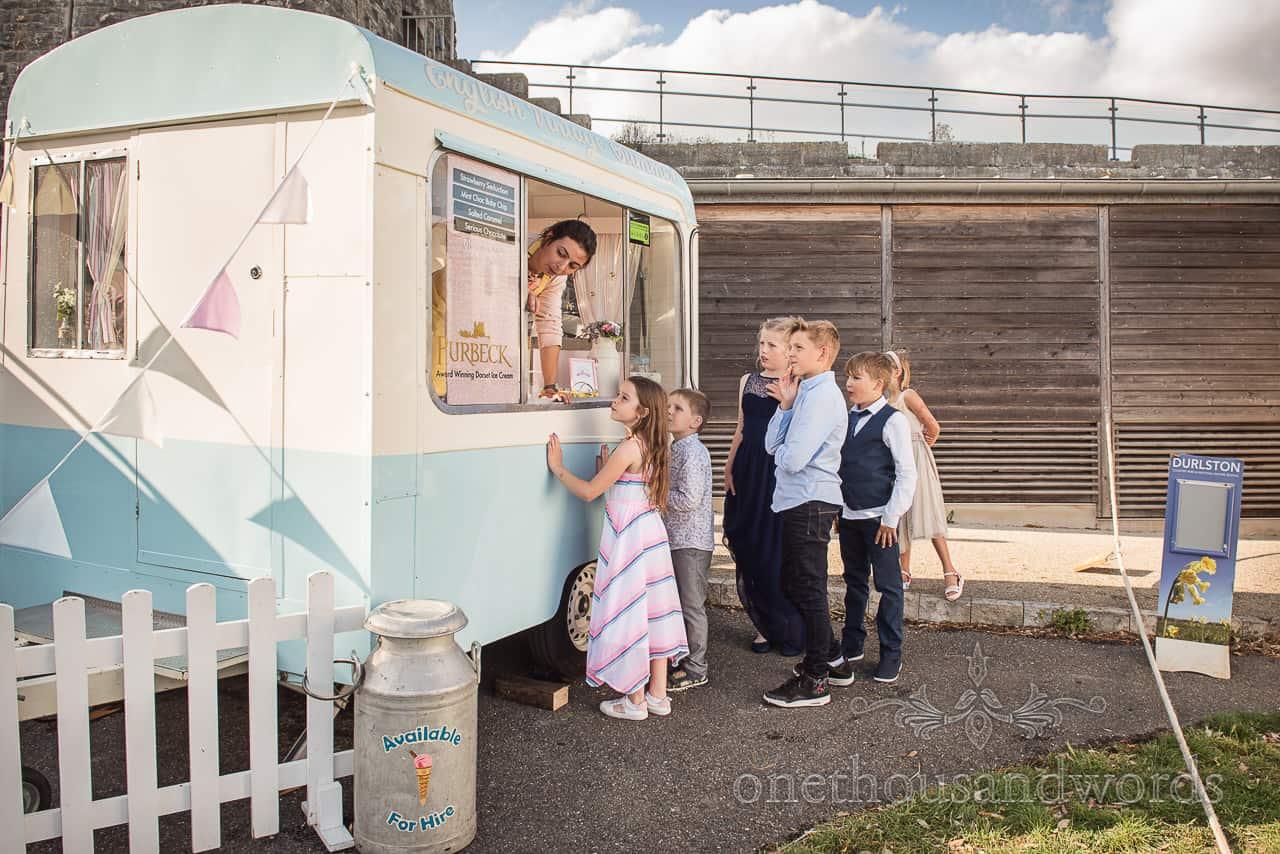 Young wedding guests queue for free Purbeck ice cream retro van at Purbeck castle wedding venue in Dorset