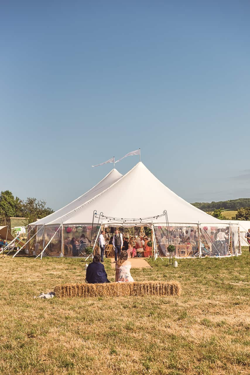 Rural Dorset countryside wedding sailcloth tent venue with straw bales photographs by one thousand words photography