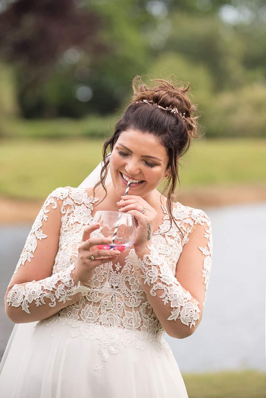 Wedding portrait photograph of happy laughing bride in detailed lace wedding dress drinking with straw by one thousand words