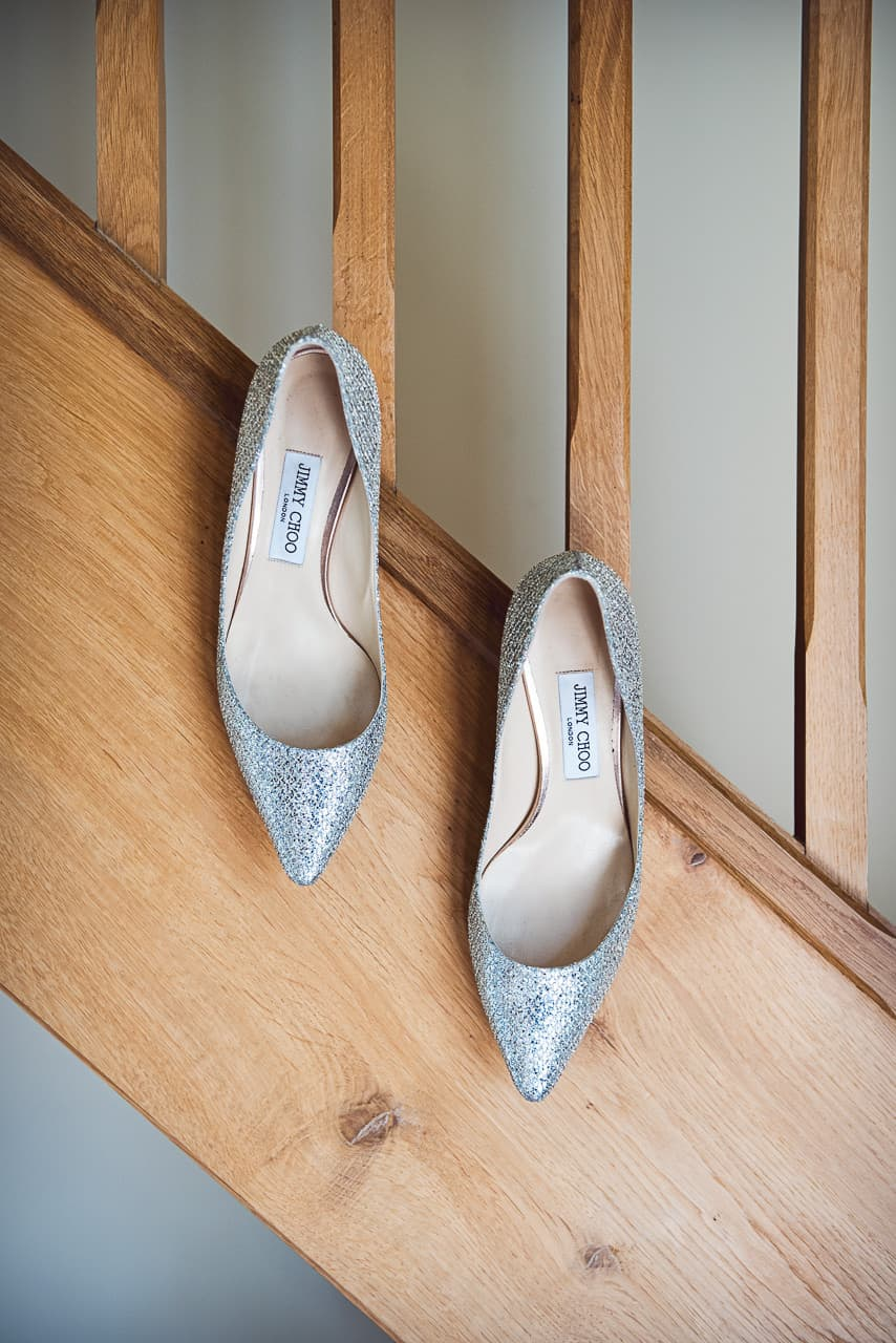 Sparkly silver Jimmy Choo wedding shoes hanging from wooden staircase wedding detail photograph by one thousand words