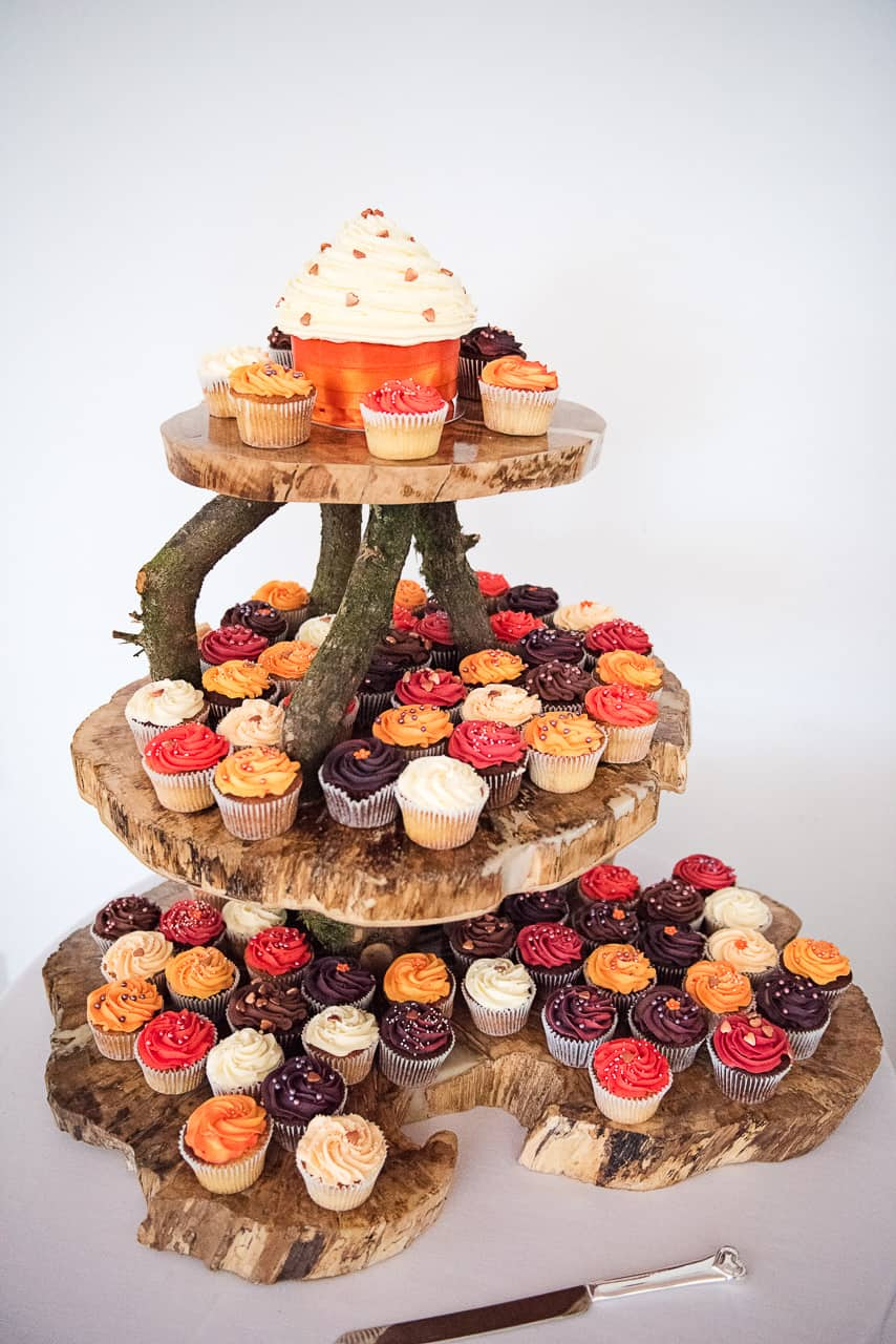 Wedding cup cakes in Autumn colours stacked on wooden slices photograph by one thousand words wedding photographers