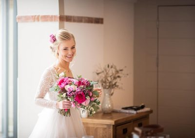 Smiling beautiful blonde bride photo with purple and red wedding flower bouquet at The Italian Villa venue in Dorset