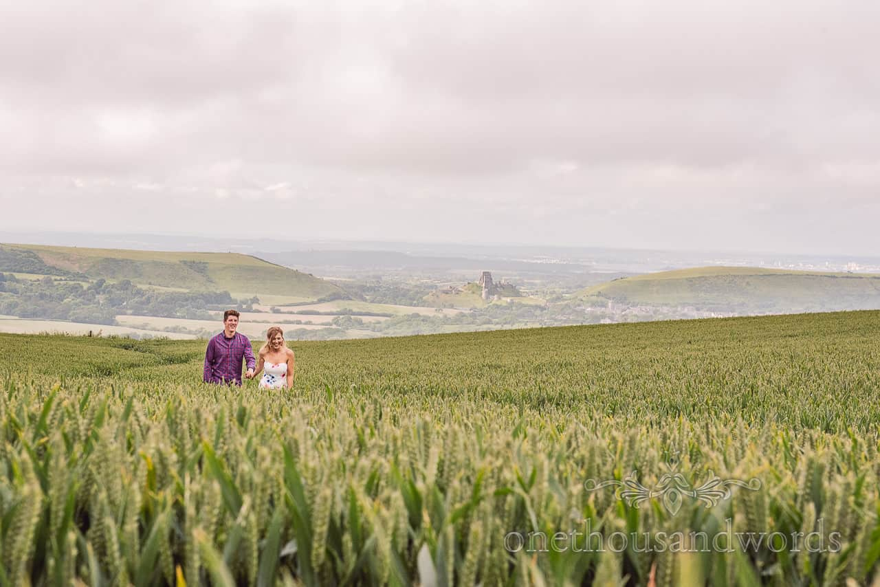 Couple walk through green wheat field in Dorset countryside with Corfe castle in the background