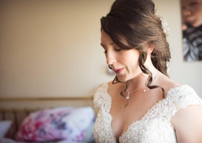 Beautiful nervous bride in white wedding dress closes eyes and takes deep calming breaths on wedding morning in Dorset