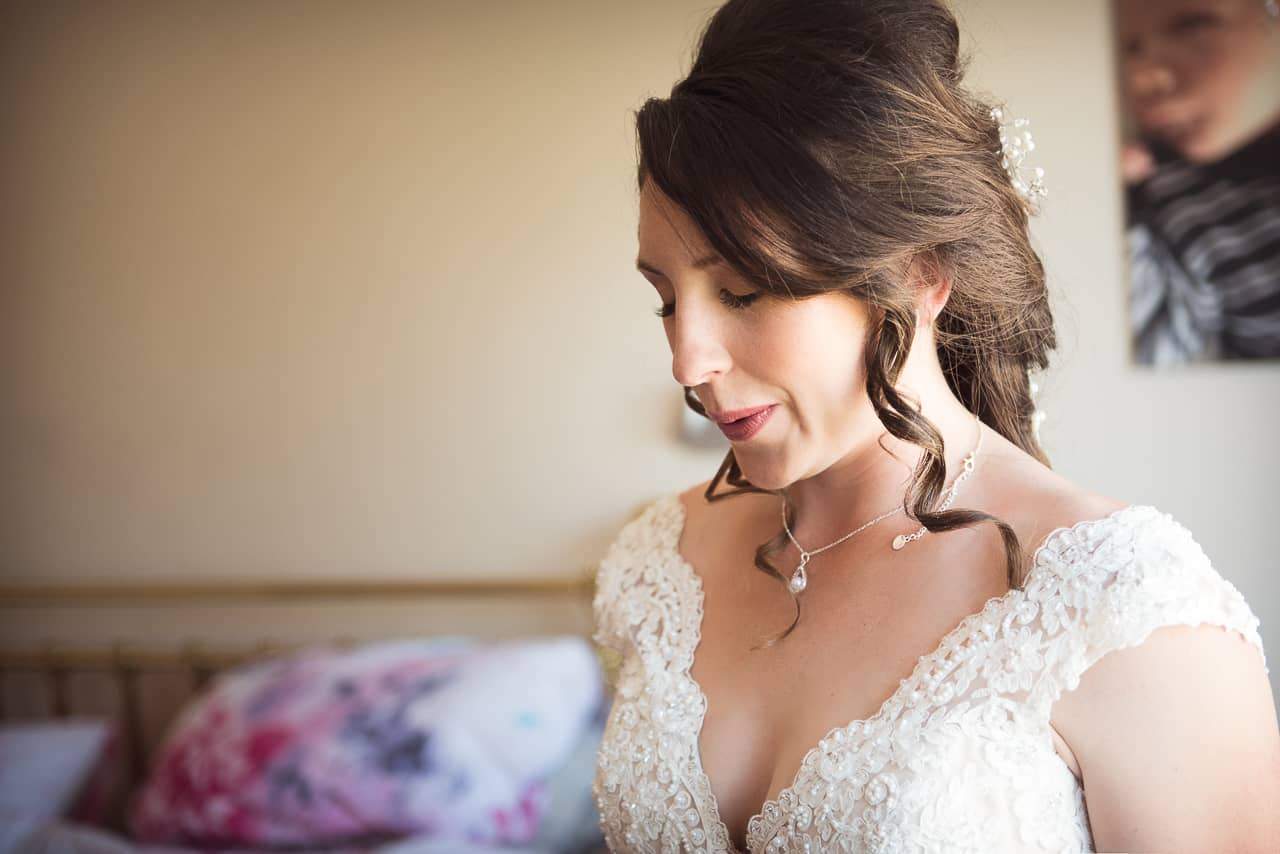Beautiful bride in white wedding dress closes eyes and takes deep calming breaths