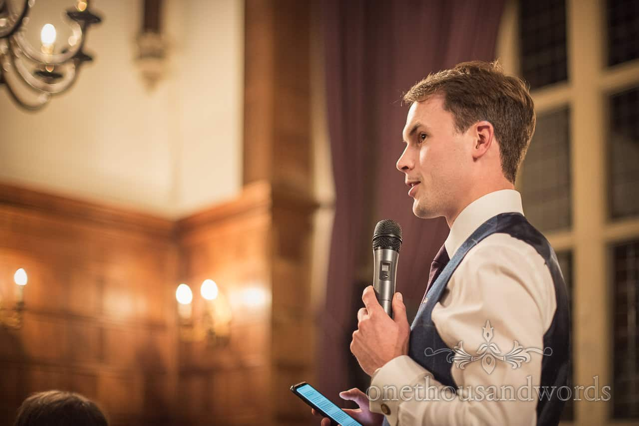 Best man in blue waistcoat reads wedding speech from mobile phone using microphone photograph by one thousand words