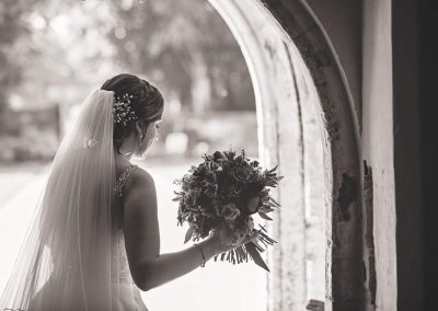 Black and white documentary wedding photo of bride with flower bouquet in stone doorway at Athelhampton House Dorset venue