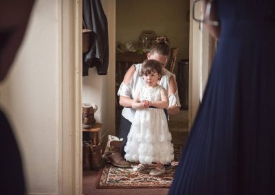 Cute flower girl is buttoned into a white wedding dress on wedding morning by one thousand words two wedding photographers