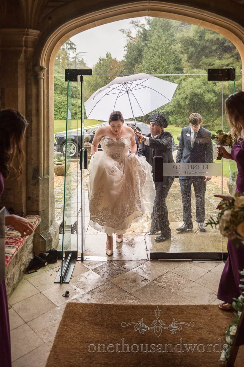 The bride arrives in rain under umbrella at New Forest Hotel wedding venue Rhinefield House hotel by one thousand words photography