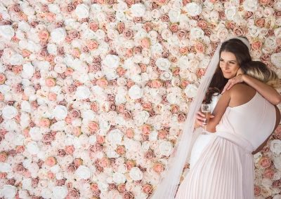 Bride and bridesmaid hug against pink and white wedding rose flower wall photograph by one thousand words photography