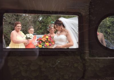 Bride and bridesmaid photograph taken through classic wedding car window by one thousand words wedding photography