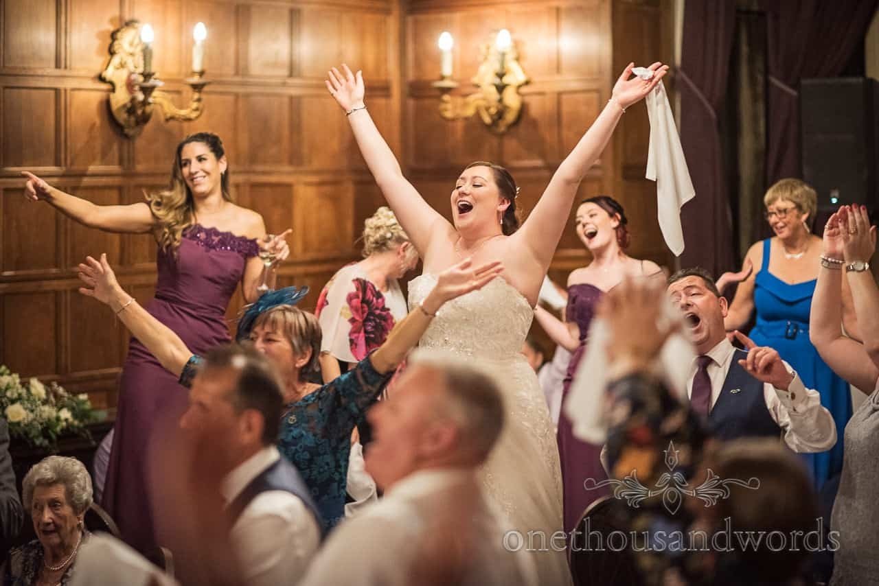 Bride, bridesmaids and guests join with singing waiters performance with hands in the air