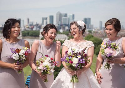 Bride and bridesmaids laughing at Greenwich Park with multi coloured floral bouquets at London summer wedding