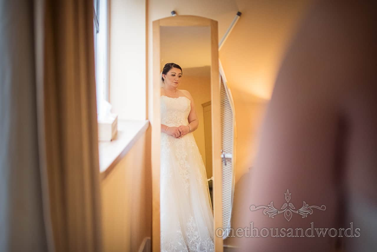 Sombre looking bride reflected in full-length mirror during bridal preparations documentary photograph