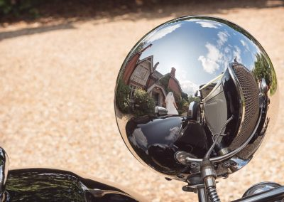 Bride classic wedding car convex wing mirror reflection at Old Vicarage Dorset wedding venue photograph by one thousand words
