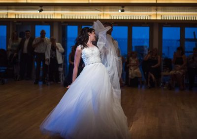 Bride pulls shapes during first dance routine under spotlight at Durlston Castle wedding venue by one thousand words photography