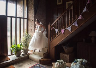 Bride descends wooden staircase with bunting on wedding morning documentary photograph by photographers with no time limits