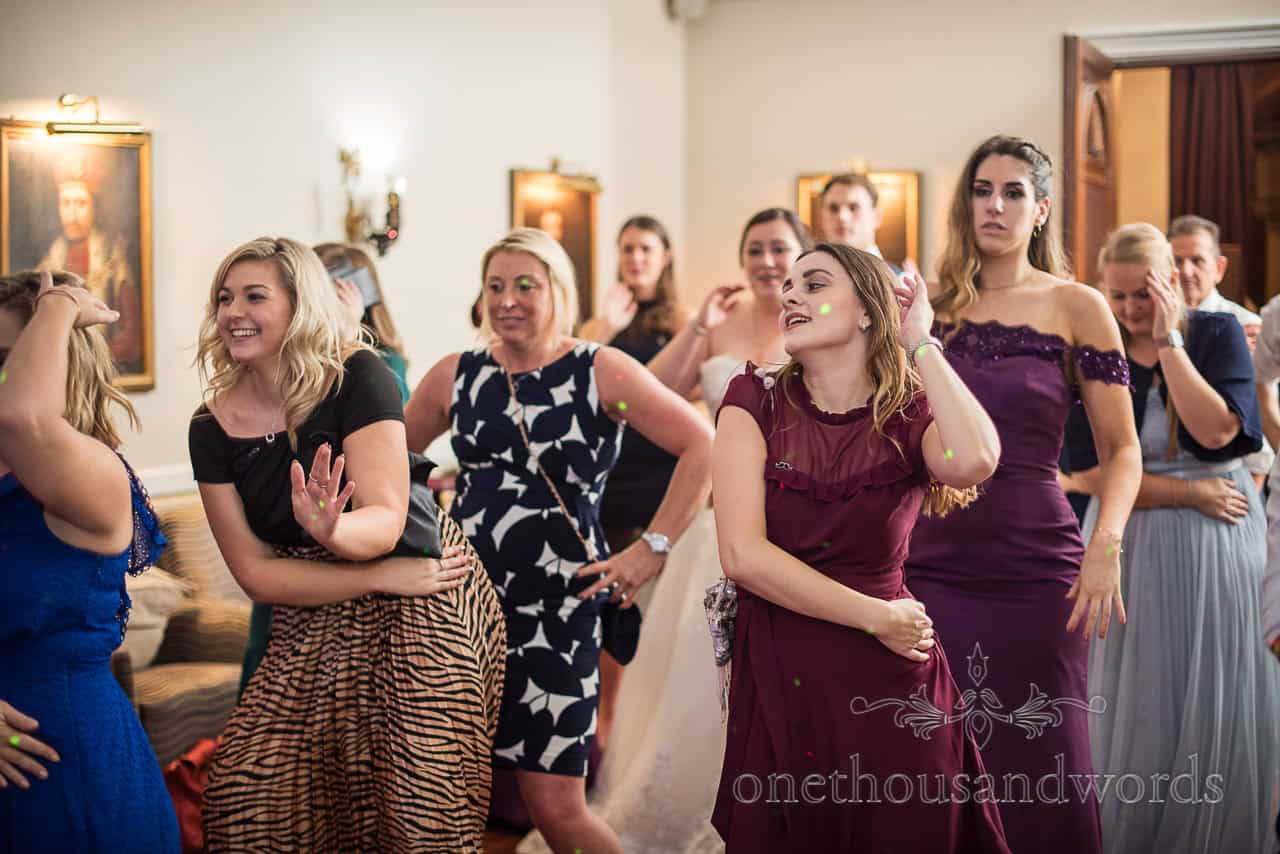 Bride and female wedding guests dancing to the Macarena on dance floor at Rinefield House hotel wedding venue in New Forest