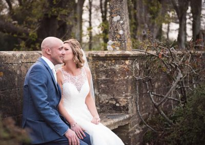 Bride and groom couple photograph kiss on cheek at on stone wall with woodland at Athelhampton House wedding venue Dorset