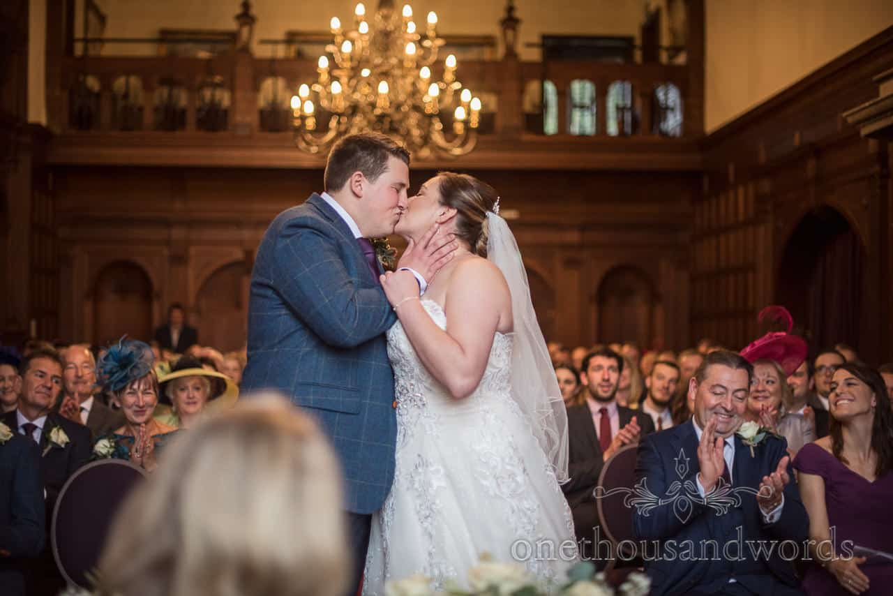 Bride and groom first kiss at New Forest hotel wedding with clapping guests at Rhinefield House