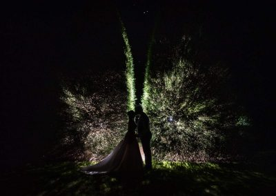 Bride and groom kiss in front of flash lit bushes at night at Athelhampton House Dorset by one thousand words wedding photography