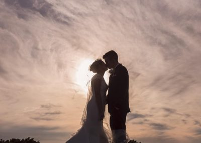 Bride and groom kissing wedding photograph with swirling evening clouds around the sun silhouette by one thousand words