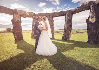 Bride and groom kissing in wood henge on bright summer's wedding day in Dorset countryside by one thousand words