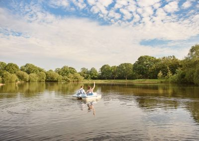 Bride and groom in pedalo at Sopley Lake summer wedding venue in Dorset by one thousand words wedding photography