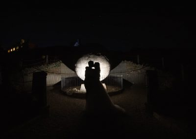 Bride and groom silhouetted against stone globe with starry night sky and glowing castle wedding venue by one thousand words