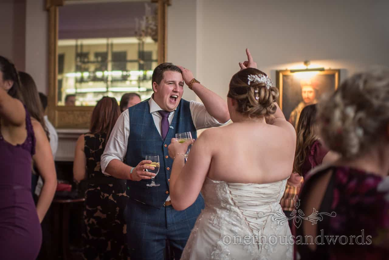 Bride and groom singing and dancing in among guests on dance floor