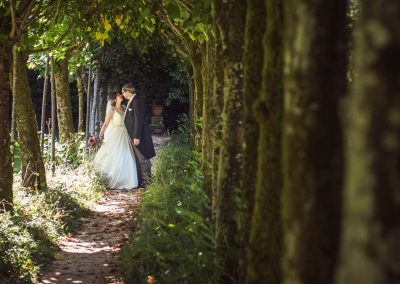 Bride and groom photographed in tree tunnel at Athelhampton House wedding venue in Dorset by one thousand words photography