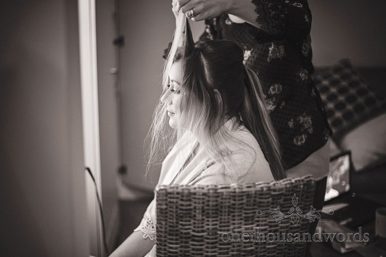Black and white documentary photograph of the bride having hair styled during wedding morning preparations