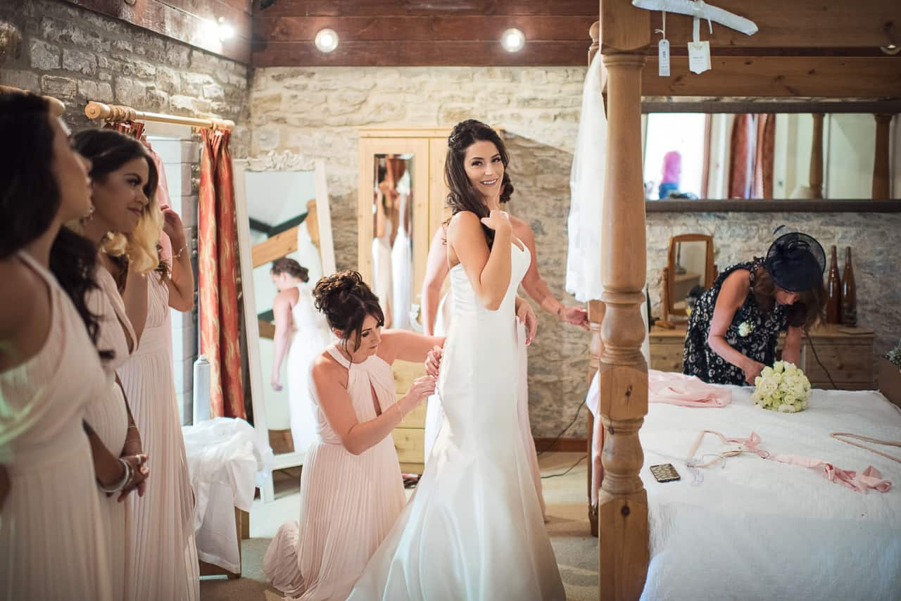 Bride laced into wedding dress by bridesmaids in pink dresses with four poster bed in bridal suite on wedding morning in Dorset